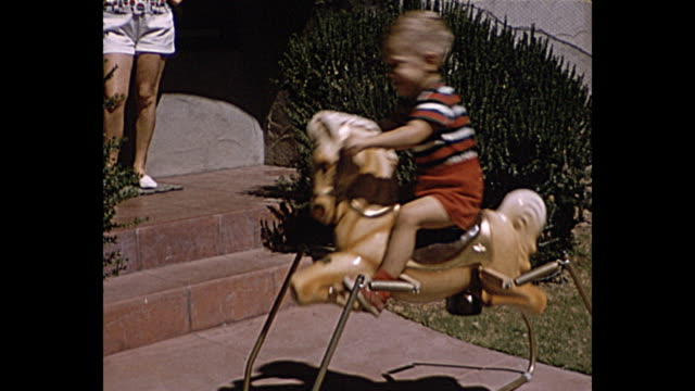 1957 summer - young boy on his rocking horse - dondolarsi video stock e b–roll