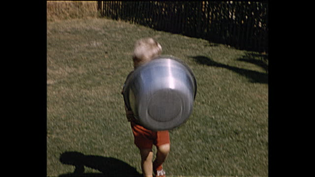 1957 summer - young boy plays with metal pot while dogs in sandbox watches him - carefree stock videos and b-roll footage