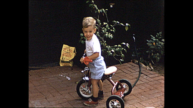 stockvideo's en b-roll-footage met 1957 summer - young boy riding his tricycle - alleen jongens