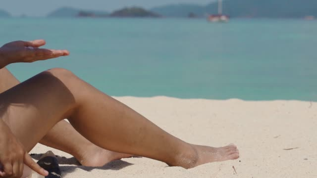 summer young woman applying the body a protective sunscreen on the beach - tan stock videos and b-roll footage