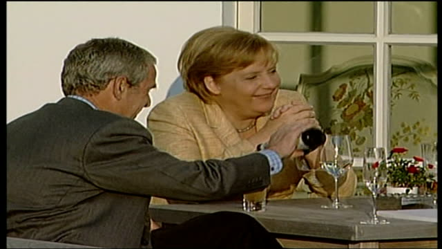 africa aid pledge criticised; germany: heiligendamm: int angela merkel sitting at dinner table beside george w bush who pours glass of non alcoholic... - alkoholisches getränk stock-videos und b-roll-filmmaterial