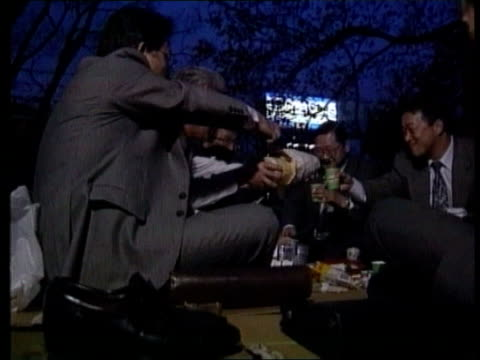 c4n report on japanese economy ext at night older worker and colleagues at cherry blossom party drinking and singing - economy stock videos & royalty-free footage