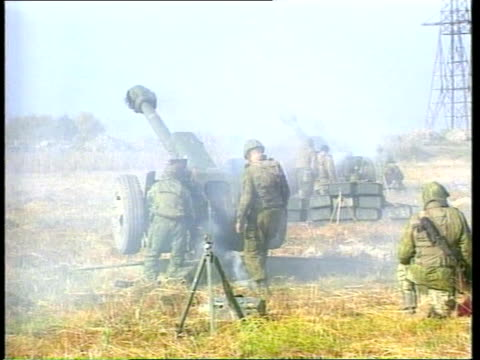 Chechnya Crisis ITN RUSSIAN FEDERATION Chechen border Russian artillery firing Soldier carrying shell across and loading artillery piece PAN Gun...