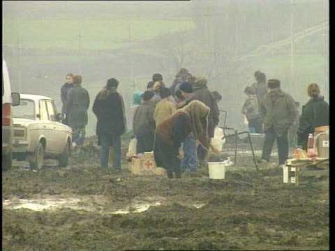 Chechnya Crisis Refugee camp People standing amidst mud in camp to collect water from standpipes People collecting water Refugees along in camp Tents...