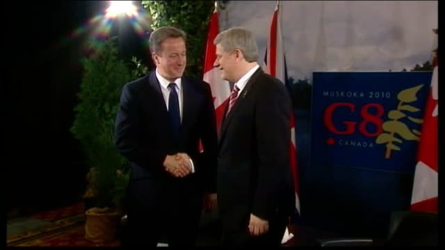 david cameron defends coalition government int cameron and harper buttoning up jackets and shaking hands for photocall angela merkel along at summit - g8 stock-videos und b-roll-filmmaterial