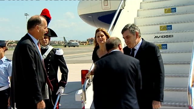 Gordon Brown arrival / photocall with Indian Prime Minister ITALY L'Aquila EXT Soldier in ceremonial uniform / Italian flag on mast fixed to plane's...