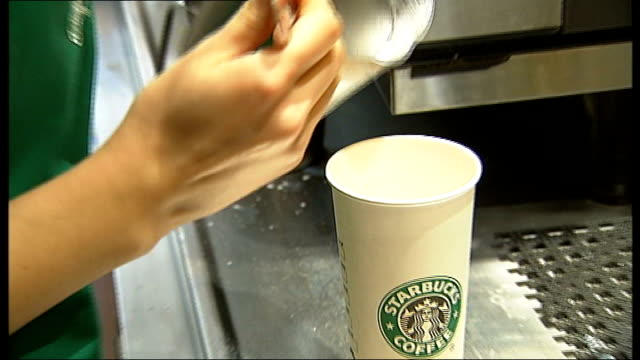 vídeos de stock, filmes e b-roll de plans for crackdown on corporate tax dodging t02121218 england london int staff in branch of starbucks operating steam wand on coffee machine hot... - starbucks