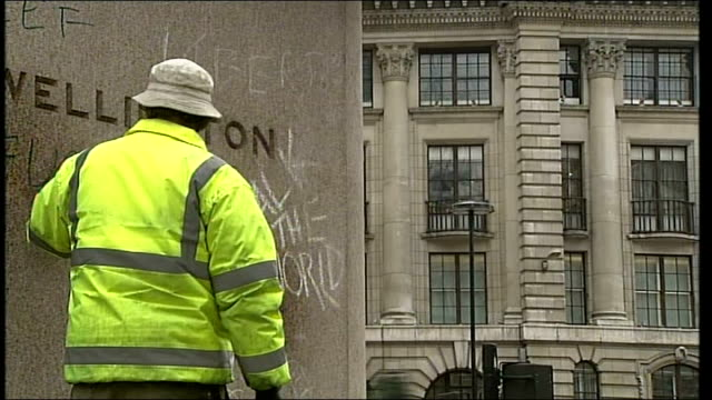 protests clean graffiti on wall the government lies the banks steal the rich laughs / workers preparing to clean up area / men cleaning up graffiti /... - sockel stock-videos und b-roll-filmmaterial