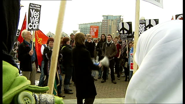 Protests Docklands near Excel Centre G20 protester beating drum Woman seated next Socialist Worker placard General view of G20 demonstration Vox pops...