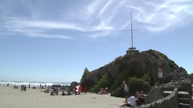 Sumner Beach with lookout tower on rock and people on beach during New Zealand summer heatwave