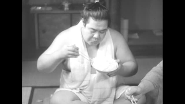 vídeos de stock, filmes e b-roll de vs sumo wrestler sits crosslegged in clubhouse with other men wearing kimonos they use chopsticks to eat from bowls - cross legged