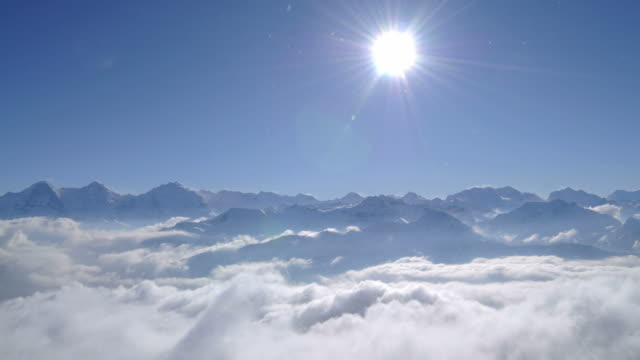 sun and blue sky over swiss alps, mountain peaks reaching out of clouds and fog