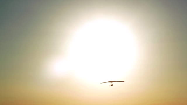 Sun and Hang gliding Flying in the Sky and Sunset