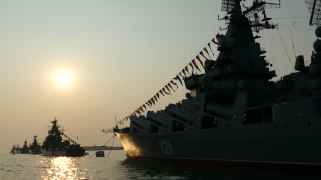 sun and the silhouettes of warships