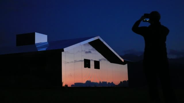 sun at dusk shine on mirage gstaad by los angelesbased artist doug aitken is on display outside as installation sculpture representing a chalet made... - ski resort stock videos & royalty-free footage
