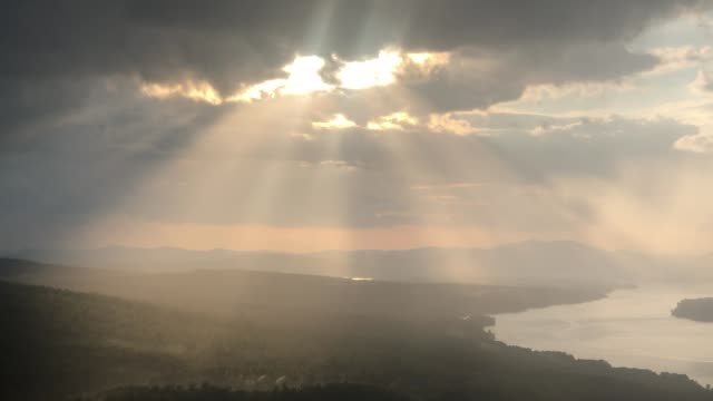 vídeos de stock e filmes b-roll de sun beams shining through clouds at the height of land lookout in rangeley, maine usa with lake mooselookmeguntic in view - território selvagem