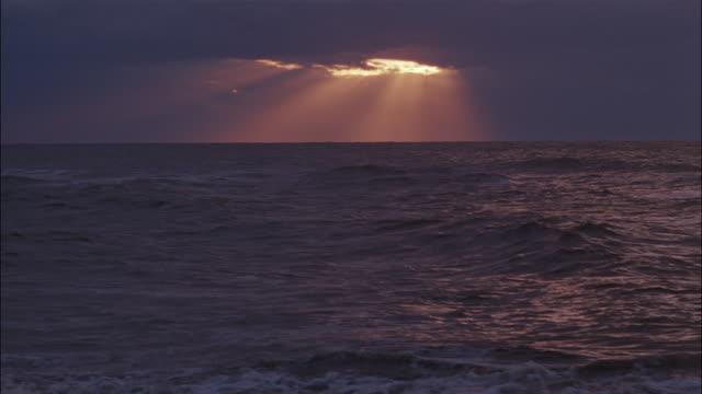 sun beams stream down from clouds above the sea. - insel sylt stock-videos und b-roll-filmmaterial