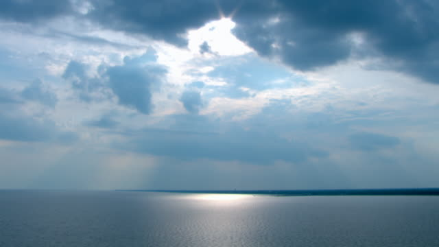 Sun beams through pale blue clouds over the calm waters of the Gulf of Mexico.