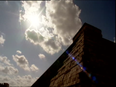 Sun blazing through clouds tilt down to top of pyramid structure Egypt