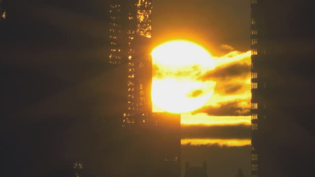 t/l cu sun breaking through clouds and rising between two mirrored buildings / new york city, usa - sunrise dawn stock-videos und b-roll-filmmaterial