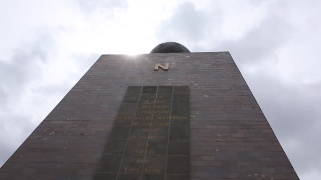 sun breaks through clouds above monument to the equator - monument stock videos & royalty-free footage