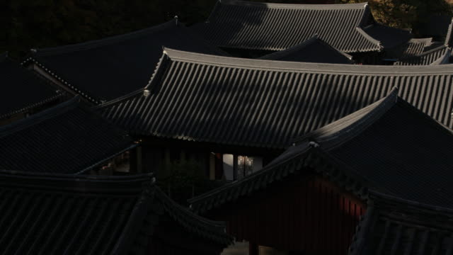 sun casting light onto the 'giwa' roof of songgwangsa temple / suncheon-si, jeollanam-do, south korea - chan buddhism stock videos & royalty-free footage