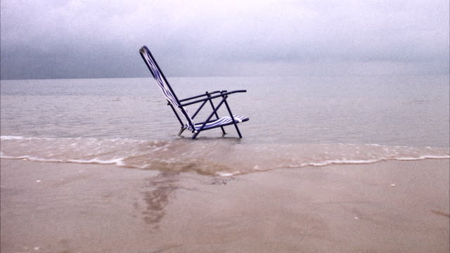 A sun chair at the waters edge Angelholm Skane Sweden.