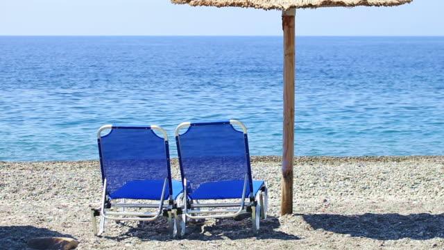 vídeos de stock, filmes e b-roll de hd: sol, cadeiras e guarda-chuva na praia - cadeira dobrável