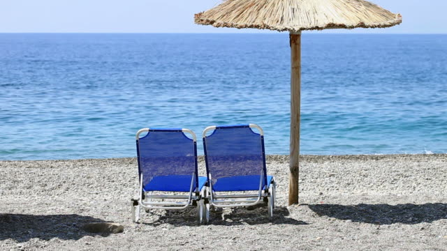 hd: sun chairs and umbrella on beach - beach chairs stock videos & royalty-free footage