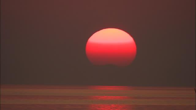 Sun changes colour as it sets over Lake Shinji, Shimane, Japan