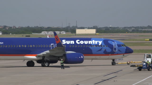 sun country passenger aircraft (boeing 737-800) pushed from gate for departure/dfw international airport, dallas-fort worth, texas, usa - dallas fort worth airport stock videos & royalty-free footage