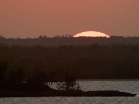 stockvideo's en b-roll-footage met ms,  sun disappearing behind sea coastline,  harbour island,  bahamas - plate met stilstaande achtergrond