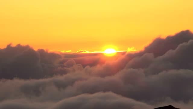 vídeos de stock, filmes e b-roll de sol desaparecer atrás das nuvens macias sobre vulcão de maui - pouca luz