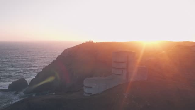 sun flare aerial drone of german observation tower from world war two at sunset, guernsey, channel islands, uk - channel islands england stock videos & royalty-free footage