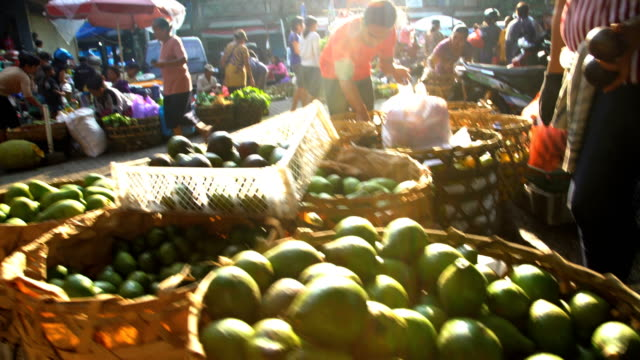 sun flare through people shopping in market indonesia - balinese culture stock videos & royalty-free footage