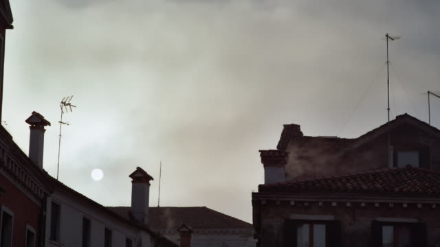 ms - sun in a misty sky, typical roof tops of venice - sun roof stock videos & royalty-free footage