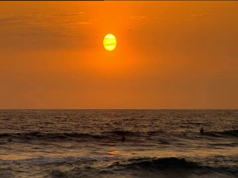 sun in orange sky above gentle rolling waves at sunset. - san diego stock videos and b-roll footage