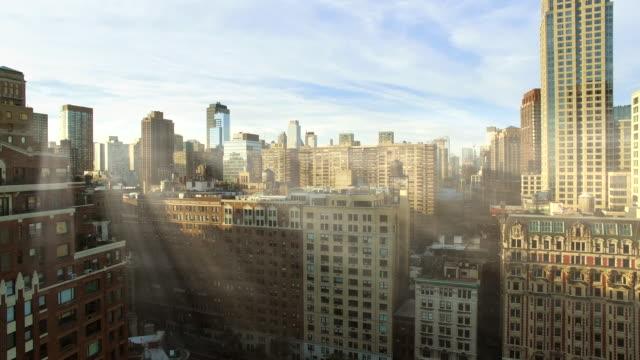 sun light beams shining through city buildings. urban metropolis background