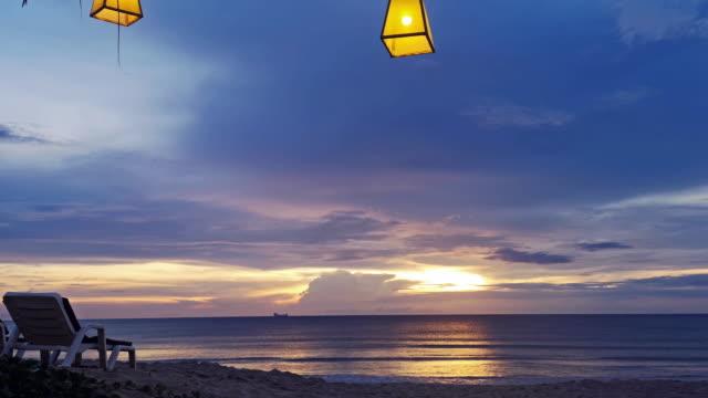 Sonnen-Lounge Stuhl-Blick auf den Sonnenuntergang am tropischen Strand mit gelben Laternen oben