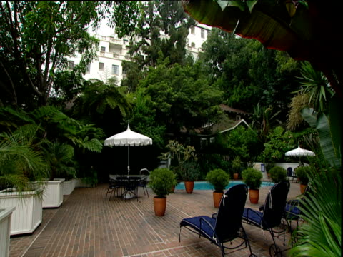 sun loungers and pool area below hotel chateau marmont in background sunset strip los angeles - 2000年風格 個影片檔及 b 捲影像