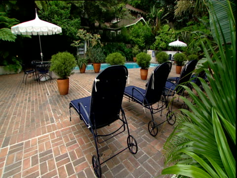 sun loungers and pool surrounded by lush garden area chateau marmont sunset strip los angeles - outdoor chair stock videos & royalty-free footage