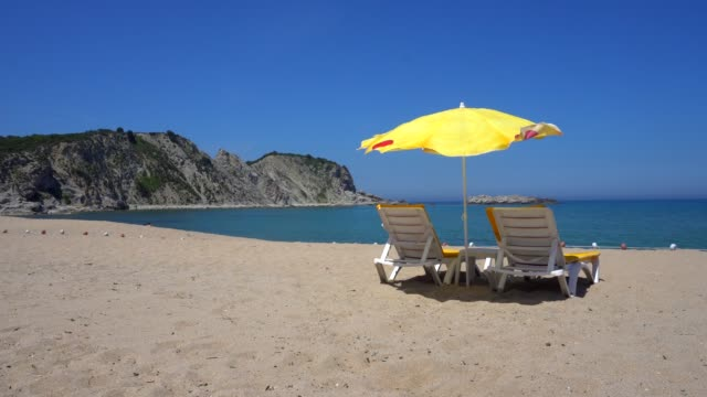 sun lounges and beach umbrellas on a beach. - deck chair stock videos & royalty-free footage