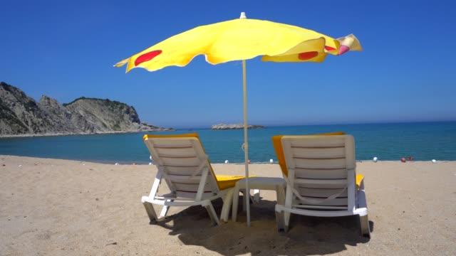 sun lounges and beach umbrellas on a beach. - beach umbrella stock videos & royalty-free footage