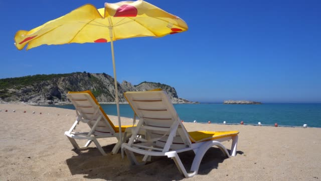 sun lounges and beach umbrellas on a beach. - deckchair stock videos & royalty-free footage
