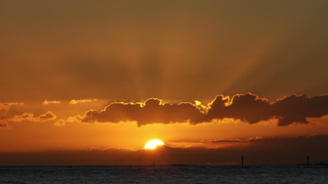 Sun over the Pacific Ocean shore of Waikiki beach in Honolulu, Oahu, Hawaii