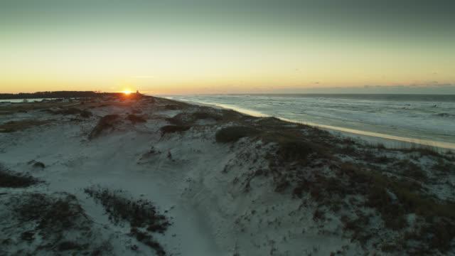 sun peeping over sand dunes at grayton beach state park, florida - florida us state stock videos & royalty-free footage