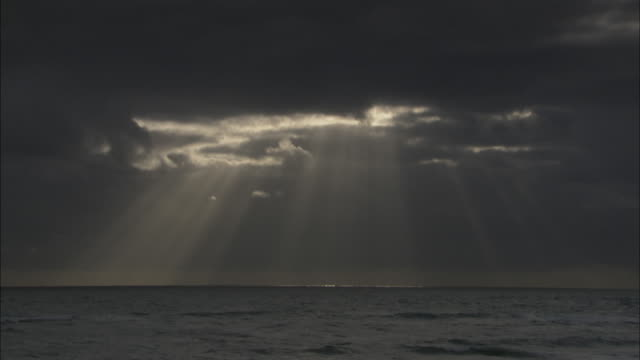 sun rays beam from a cloudy sky over an ocean. - grey colour stock videos & royalty-free footage