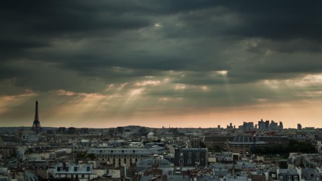 Sun rays beam through storm clouds over Paris landmarks.