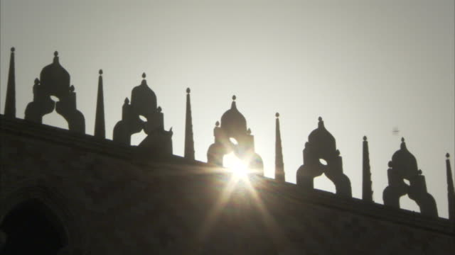 sun rays beam through the gothic ornamentation on the roof of the doge's palace on the piazza san marco in venice italy. available in hd. - tetto video stock e b–roll