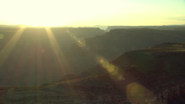 Sun rays stream over the Grand Canyon at sunset.